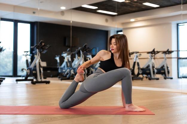 Jonge vrouw die uitrekkende oefeningen in gymnastiek doet