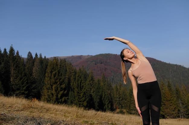 Jonge vrouw die uitrekkende oefeningen op aard in bergen doet. sport meisje beoefenen van yoga pose in beenkappen. prachtig boslandschap