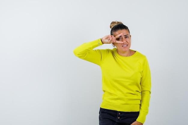 Jonge vrouw die v-teken op oog in gele sweater en zwarte broek toont en gelukkig kijkt