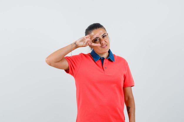 Jonge vrouw die v-teken op oog in rood t-shirt toont en mooi kijkt. vooraanzicht.