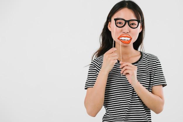 Jonge vrouw die valse glazen en lippen uitproberen