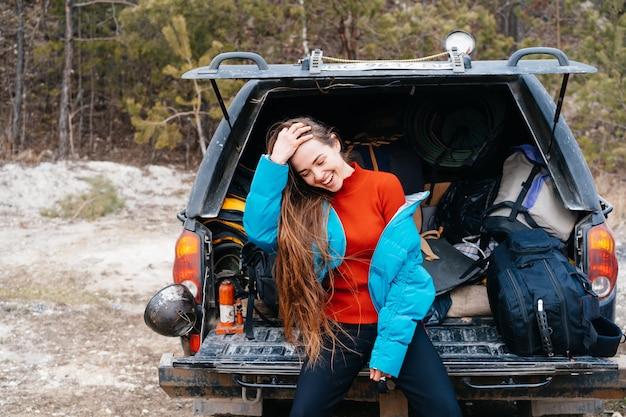 Jonge vrouw die van aard geniet terwijl het zitten in de autoboomstam