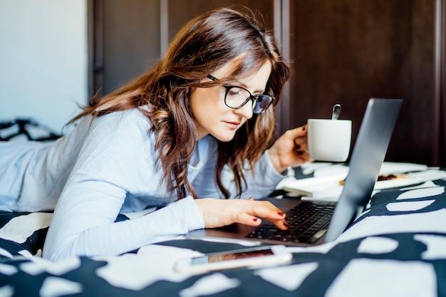Jonge vrouw die van bed thuis met computer werkt.