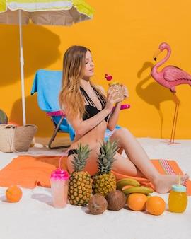 Jonge vrouw die van cocktail op strand geniet