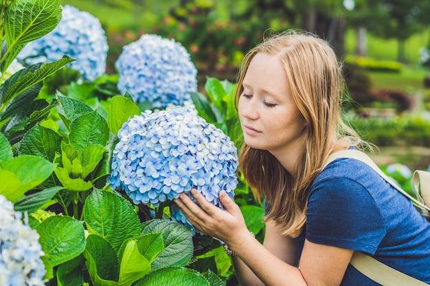 Jonge vrouw die van de geur van hortensia geniet.