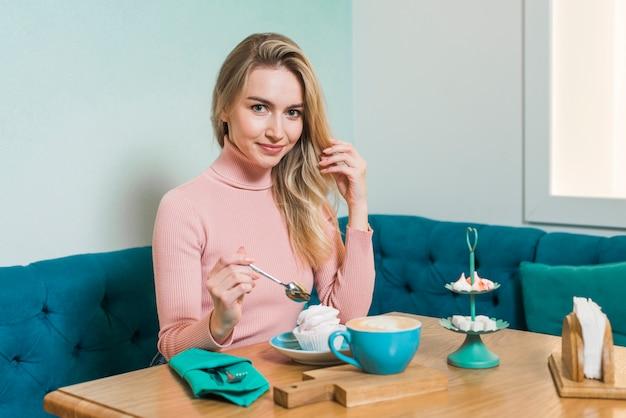 Jonge vrouw die van de meringue en cappuccinokoffie geniet in caf�