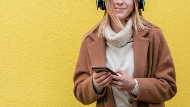 Jonge vrouw die van de muziek op haar hoofdtelefoons met exemplaarruimte geniet