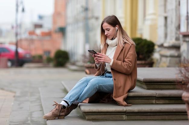 Jonge vrouw die van de muziek op haar oortelefoons in de stad geniet