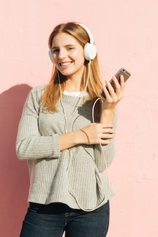 Jonge vrouw die van de muziek op hoofdtelefoon door smartphone genieten tegen roze achtergrond