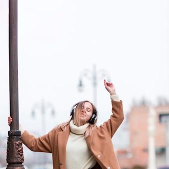Jonge vrouw die van de muziek op hoofdtelefoons in de stad geniet