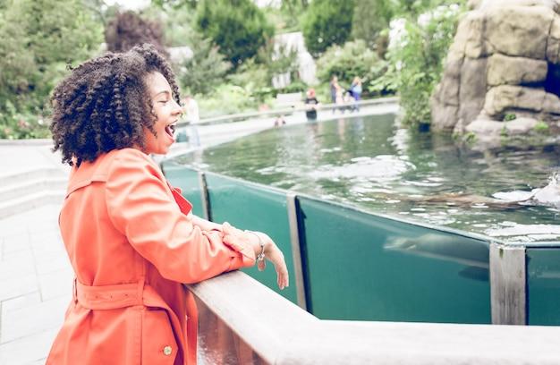 Jonge vrouw die van de show genieten bij de dierentuin met zeeleeuwen Premium Foto