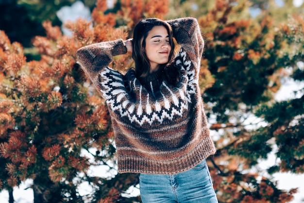 Jonge vrouw die van de sneeuwbergen in de winter geniet