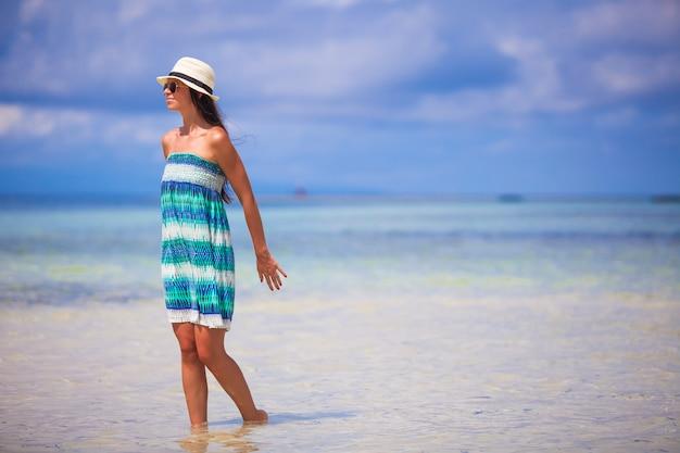 Jonge vrouw die van de vakantie op een wit, tropisch strand geniet bij zonnige dag