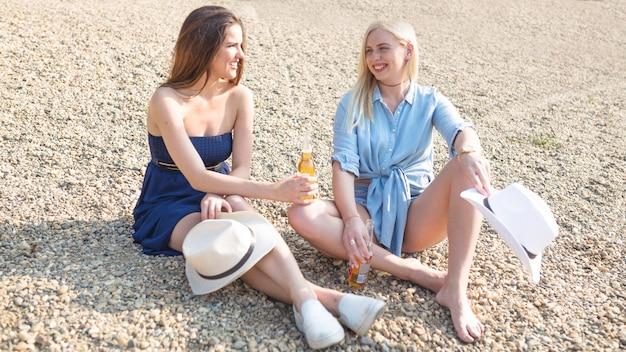 Jonge vrouw die van de zitting van het fruitbier op strand geniet