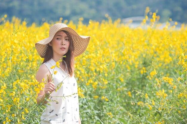 Jonge vrouw die van de zomer op geel gebied geniet