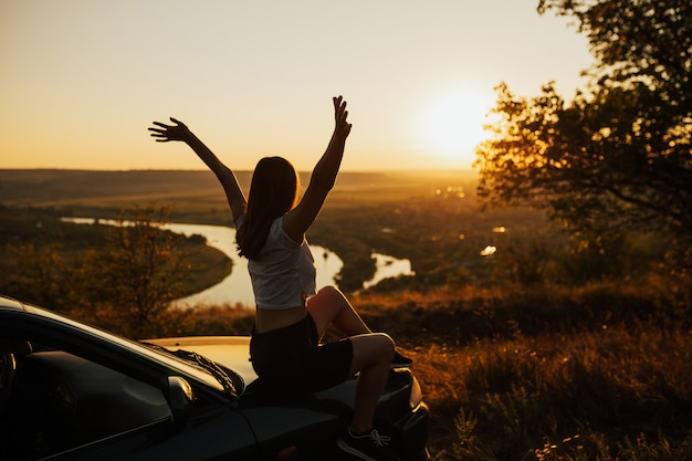 Jonge vrouw die van de zonsondergang op auto geniet. reizen met de auto bij zonsondergang
