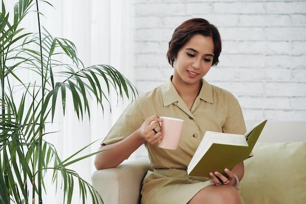 Jonge vrouw die van een boek geniet