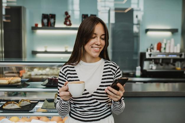 Jonge vrouw die van een koffiekop geniet