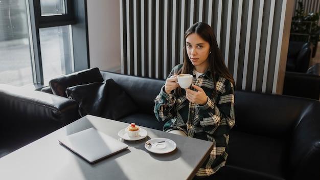 Jonge vrouw die van een koffiepauze geniet