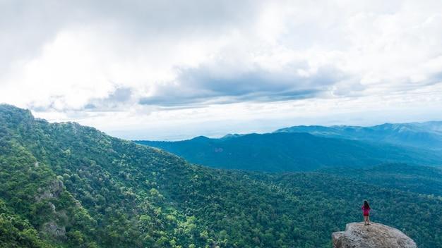 Jonge vrouw die van een valleimening vanaf bovenkant van een berg geniet.