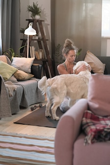 Jonge vrouw die van haar huisdier houdt terwijl ze op de vloer in de woonkamer zit