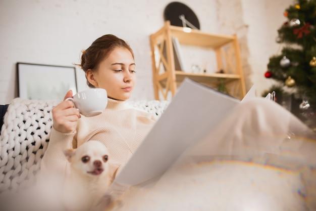 Jonge vrouw die van haar huiselijk leven geniet. thuiscomfort, winter en vakantietijd