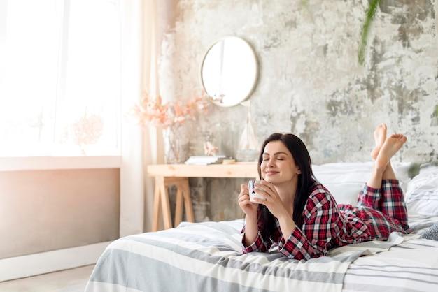 Jonge vrouw die van haar ochtend in bed geniet