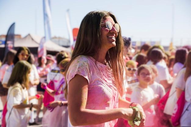 Jonge vrouw die van het spelen van holi met kleuren geniet
