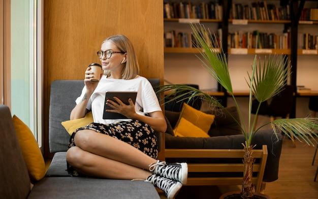 Jonge vrouw die van koffie geniet in de bibliotheek