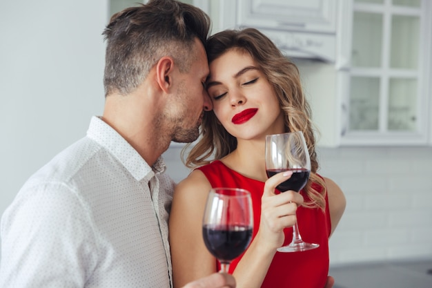 Jonge vrouw die van kussen van haar knappe man geniet