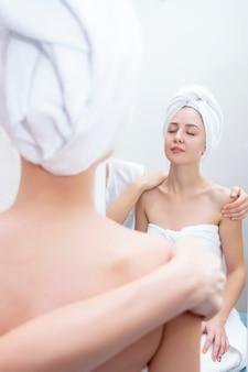 Jonge vrouw die van massage in kuuroordsalon geniet. massage en lichaamsverzorging. spa lichaamsmassage vrouw handen behandeling. vrouw die massage in de kuuroordsalon heeft voor mooi meisje. verticale foto