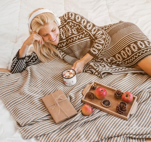 Jonge vrouw die van muziek en hete drank op bed geniet