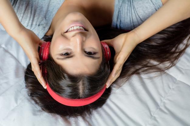 Jonge vrouw die van muziek op bed geniet.