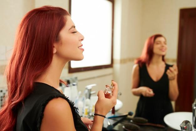 Jonge vrouw die van nieuwe geur geniet
