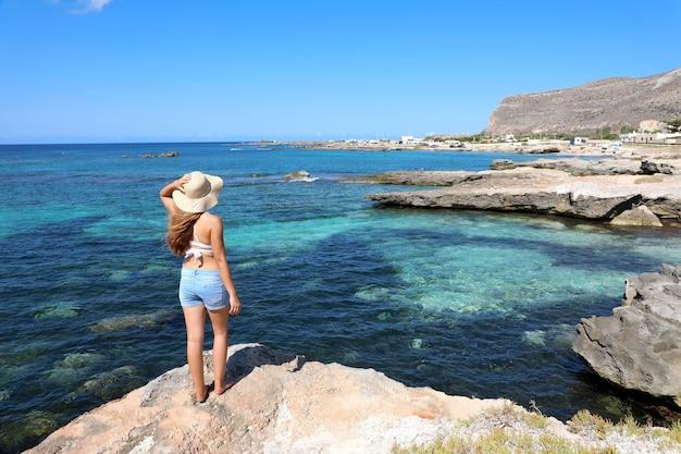 Jonge vrouw die van vakantie geniet in favignana-eiland, sicilië, italië