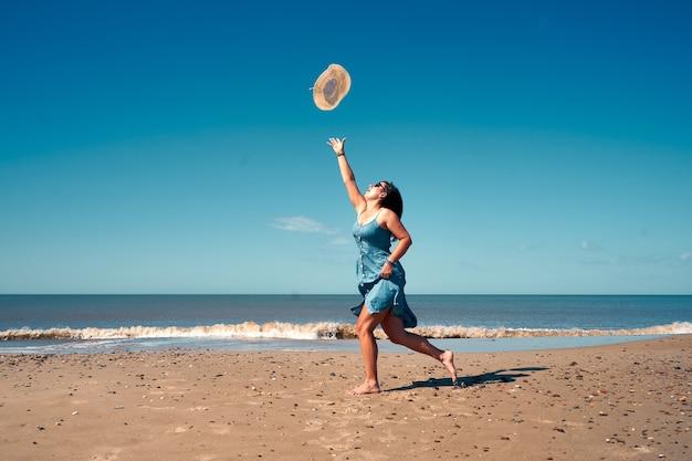 Jonge vrouw die van vrije tijd op het strand geniet en de hoed inhaalt