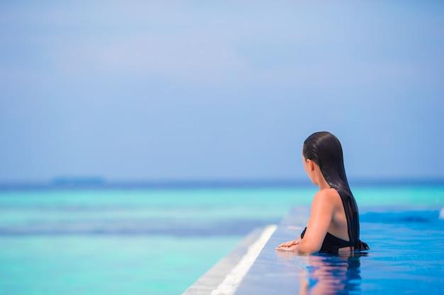 Jonge vrouw die van water en rust in openlucht zwembad geniet