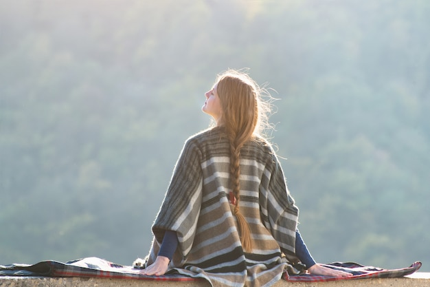 Jonge vrouw die van zonnige dagzitting op een heuvel geniet. gesloten ogen. achteraanzicht