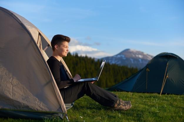Jonge vrouw die van zonsopgang in de bergen genieten die in haar tent zitten die aan laptop werken