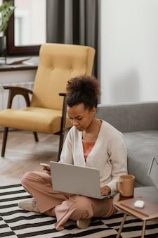 Jonge vrouw die vanuit modern huis werkt