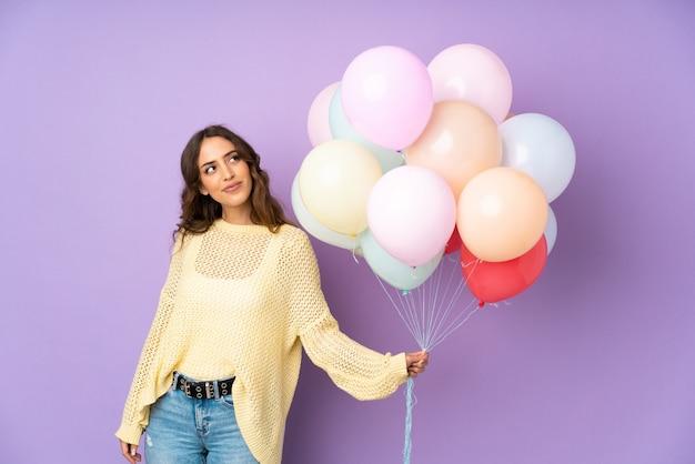 Jonge vrouw die veel ballons over op purpere en muur vangen die omhoog lachen kijken