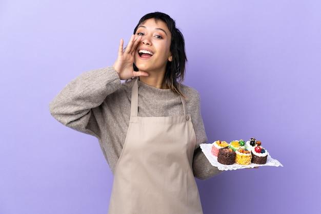 Jonge vrouw die veel verschillende minicakes over geïsoleerde purpere schreeuwen houden met wijd open mond