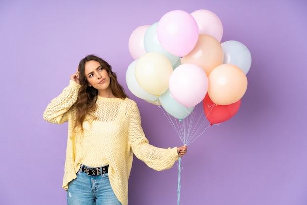 Jonge vrouw die vele ballons bij het hebben van twijfels en met verwarren gezichtsuitdrukking vangt