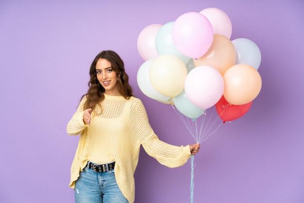 Jonge vrouw die vele ballons over geïsoleerd op purper muurhandenschudden vangen na goede deal