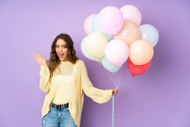 Jonge vrouw die vele ballons over geïsoleerd op purpere muur met verrassingsgelaatsuitdrukking vangt