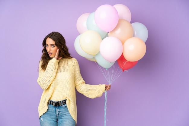 Jonge vrouw die vele ballons over geïsoleerd op purpere muur vangen die iets fluisteren