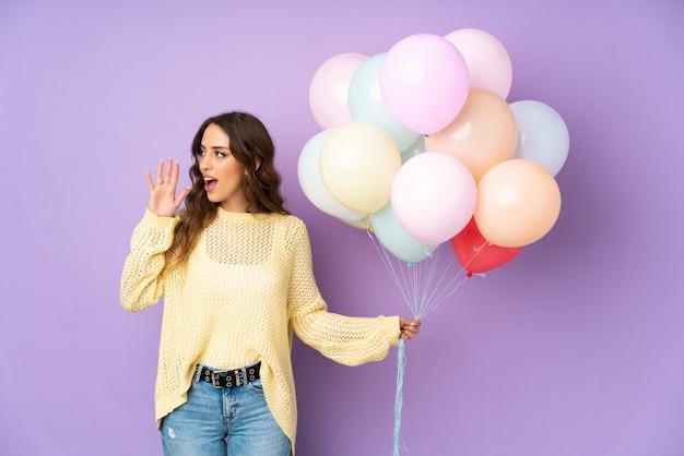 Jonge vrouw die vele ballons over geïsoleerd op purpere muur vangen die met wijd open mond schreeuwen
