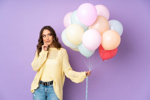 Jonge vrouw die vele ballons over geïsoleerd op purpere muur vangt die een idee denkt