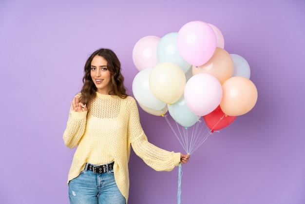 Jonge vrouw die vele ballons over geïsoleerd op purpere muur vangt die een ok teken met vingers tonen