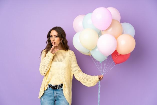 Jonge vrouw die vele ballons over geïsoleerd op purpere muur vangt die stiltegebaar doet